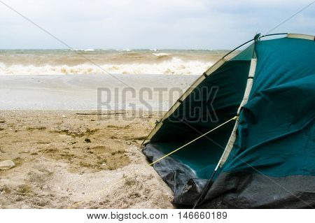 A closeup of a camping tent set up close to the water's edge on a beach. The sand is damp from bad weather and strong winds are blowing at the tent.