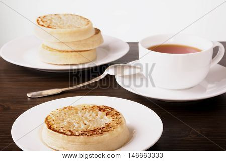 Tea and crumpets on a dark wooden table