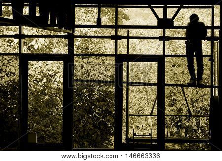 Sepia silhouette of a resting worker through a large window facing toward the outdoors.