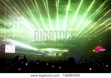 A night outdoor party with green laser show. Fan shaped pattern with silhouetted crowds below.