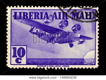 Liberia - CIRCA 1938: A stamp printed in Liberia shows three-engine aircraft over the ocean, circa 1938