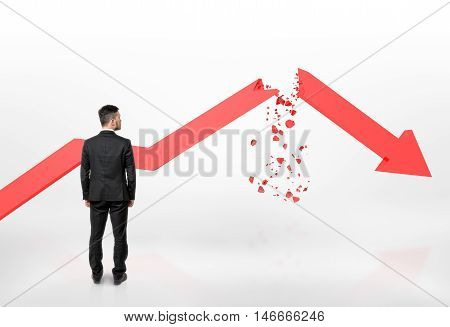 Back view of a businessman looking at red broken arrow of falling graph isolated on white background. Stock market selloff. Economic crisis. Bad luck and problems.