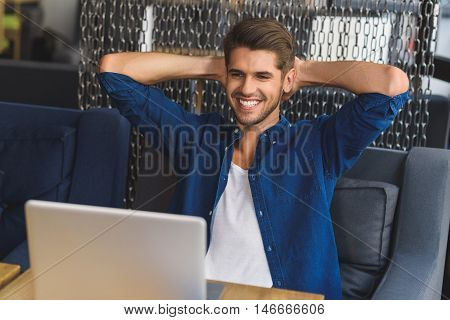 I did it, man sitting in front of laptop with cheerful smile on his face