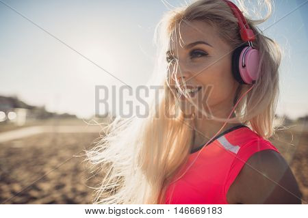 Portrait of young beautiful woman listening to music at beach. Close up face of smiling blonde woman with earphone looking at camera. Girl running at beach and listening to music