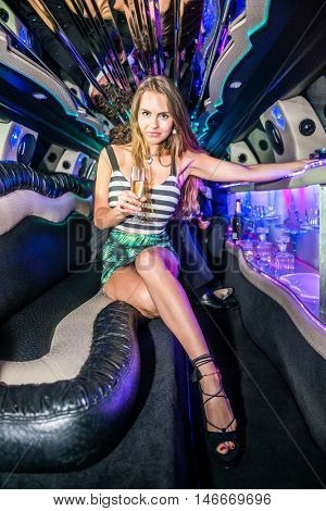 Elegant Young Woman Holding Champagne Flute In Limousine