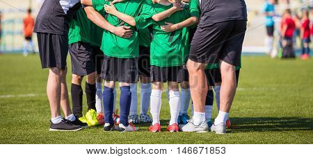 Football soccer match for children. Coach giving young soccer team instructions. Youth soccer team together before final game. Football match for children. Boys group shout team gathering. Coach briefing. Soccer football background.