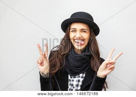 Smiling urban girl with smile on her face. Portrait of fashionable gir wearing a rock black style having fun outdoors in the city