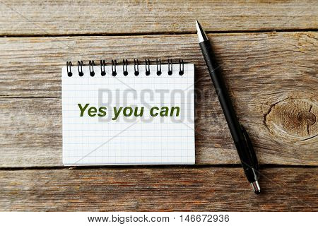 Notebook on grey wooden background, yes you can