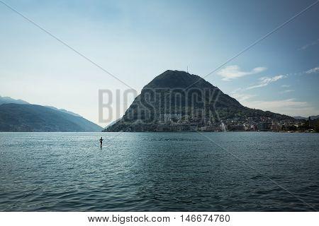 A man alone paddling over the surfboard Lugano Switzerland