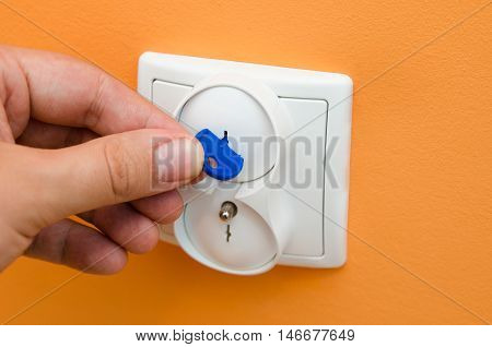 Man puts electrical security plugs for baby and child safety