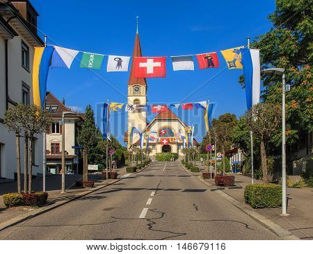 Wallisellen, Switzerland - 10 September, 2016: Kirchstrasse street decorated with flags, Protestant Church in the background. Wallisellen is a municipality in the district of Bulach in the Swiss canton of Zurich.