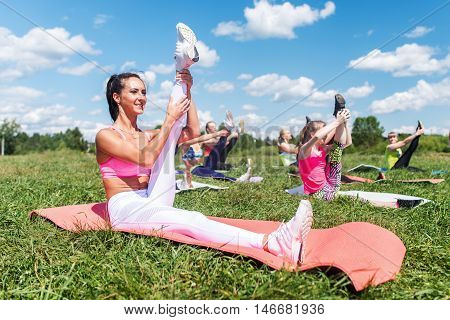 Fit women doing exercises stretching hamstrings lifting legs fitness class in parkland.