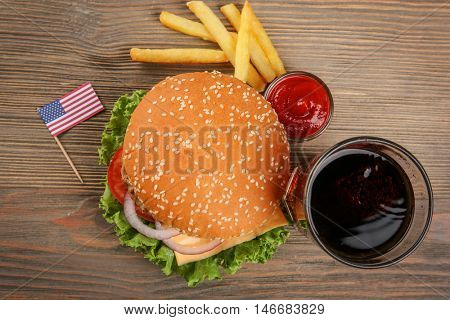 Tasty cheeseburger with snack and coke on wooden table