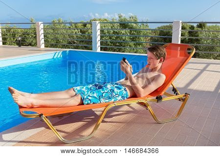 Caucasian youngster lying on sunlounger operating mobile phone at swimming pool