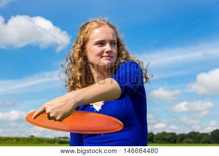 Young caucasian woman holding orange frisbee outdoors against blue sky