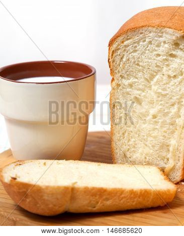 A loaf of white bread and a cup of milk