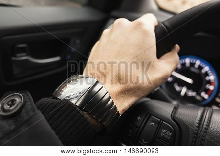 Driver Hand With Wrist Watch On A Steering Wheel