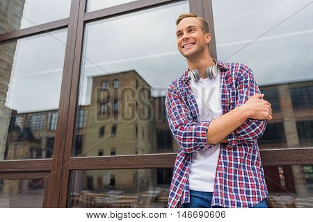 Loving life in city. Happy guy with headphones standing near windows of building outside and smiling with his hands folded