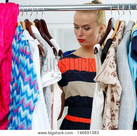 Thoughtful Sad Blonde Woman Stand Near Wardrobe Rack Full Of Clothes