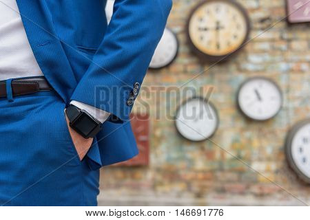 Time in the modern age. Close up of businessman with smartwatches wearing in blue suit and keeping his hand in pocket