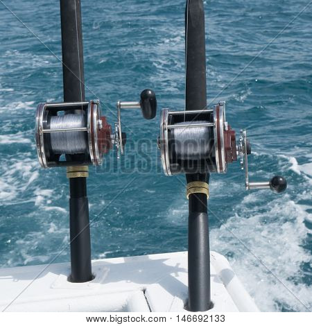 Fishing rods on a boat over blue sea. Picture of two fishing rods in pole holders on the back of a boat