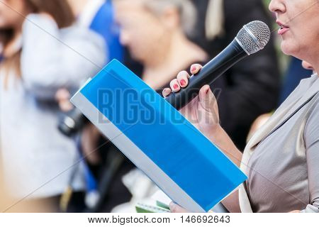 Speaker with microphone in hand at meeting closeup