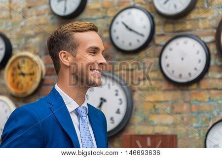 Dreaming up new ideas. Portrait of confident young businessman standing against brick wall, looking ahead and smiling