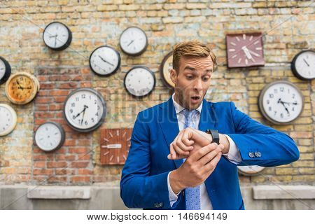 I am late. Shot of handsome young businessman looking stressed while checking his watch in front of brick wall