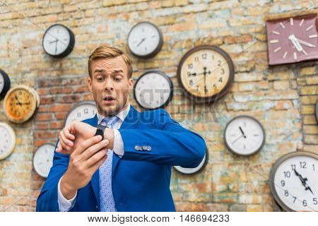 I need help. Corporate businessman checking time, looking on his smartwatch against brick wall and so much worrying