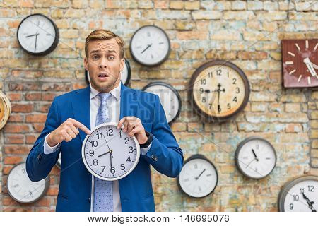 Make deadline every time. Portrait of confused young man holding clock in hand with brick wall on background