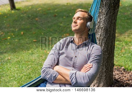 Relaxing with good music. Young man relaxing in hammock and listening to music on headphones in park