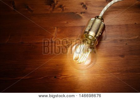 LED filament classic styled bulb on wooden board background.