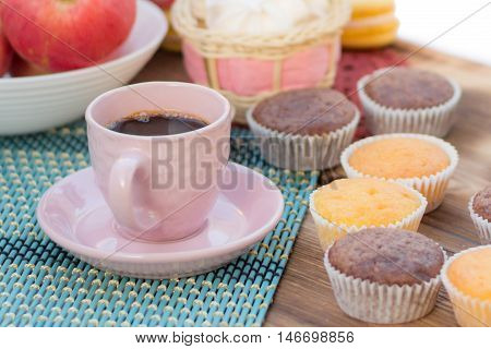 Still life of served coffee cups cup-cakes marshmallows and apples
