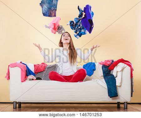Happy woman sitting on sofa couch in messy living room throwing clothes. Young girl surrounded by many stack of clothing. Disorder and mess at home. poster