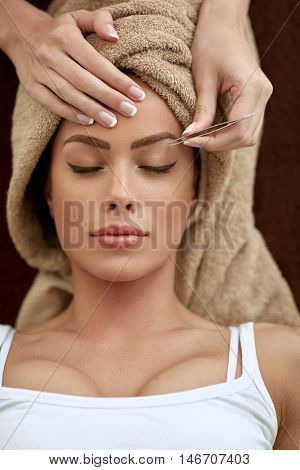 Young women having treatment plucking eyebrows at beauty salon