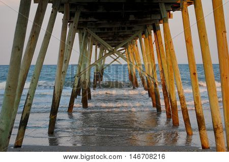 Ocean Pier - Underneath view of a wooden pier with dusk sunset light shimmering off the poles and water of the ocean's edge.