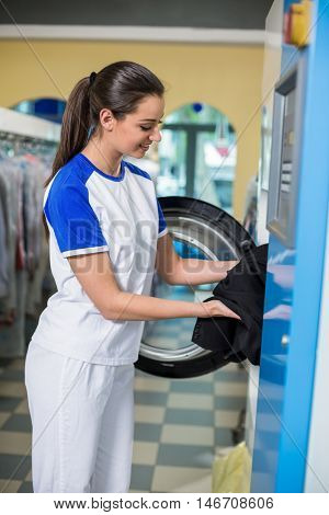 Employees putting clothes in the dryer in dry cleaner