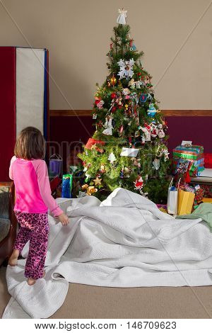A little girl sneaks into the living room on Christmas morning before her presents from Santa Claus have been uncovered.