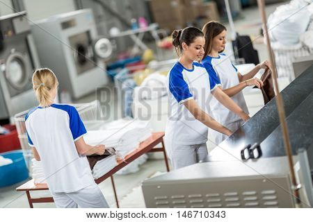 Back view worker agrees ironed textile in dry cleaner