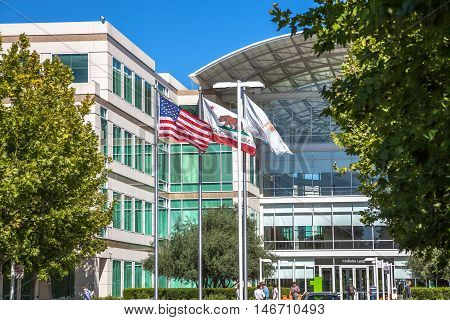 Cupertino, CA, USA - August 15, 2016: flags in front of Apple Headquarters with American Flag and flag with Apple icon. Apple is a multinational in Silicon Valley that produces technology devise.