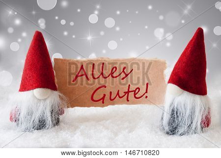 Christmas Greeting Card With Two Red Gnomes. Sparkling Bokeh And Noble Silver Background With Snow. German Text Alles Gute Means Best Wishes