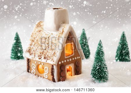 Gingerbread House In Snowy Scenery As Christmas Decoration. Christmas Trees And Candlelight For Romantic Atmosphere. Gray Background With Snowflakes. Christmas Card For Seasons Greetings