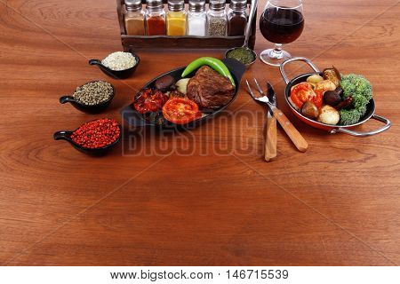 fresh roast beef meat rib eye steak with tomatoes,potatoes, hot chili pepper green  and pink peppercorn saucer, cutlery, set of spice, and red wine glass on light walnut table