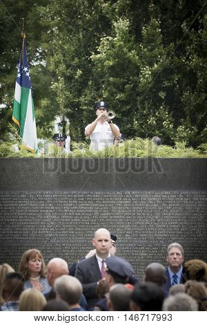 NEW YORK - SEPT 9 2016: A police officer plays Taps on the trumpet at the end of the NYPD 9/11 Memorial Commemoration Service on the 15th anniversary of the terror attacks at the NYC Police Memorial.