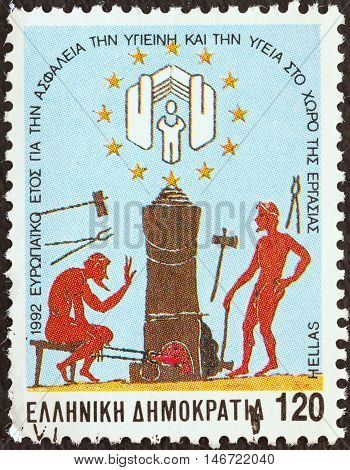 GREECE - CIRCA 1992: A stamp printed in Greece issued for the European year of social security, hygiene and health in the workplace shows Hephaestus's forge (6th century B.C. urn), circa 1992.
