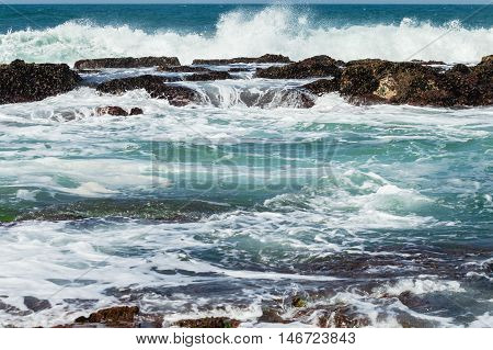 Rocky ocean coastline tidal water pools waves crashing landscape.