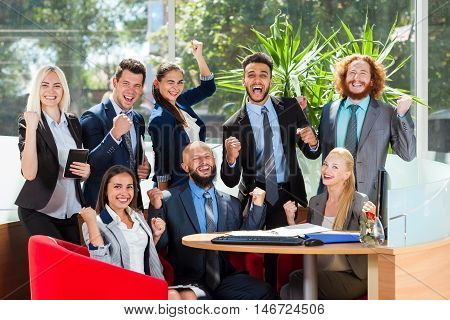 Business People Group Sit At Desk, Successful Excited Team In Modern Office, Businesspeople Happy Smile With Raised Hands Fists Arms Up