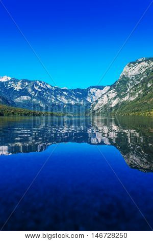 Bohinj lake in Slovenian national park Triglav with its clear water surface surrounded with Julian Alps mountains