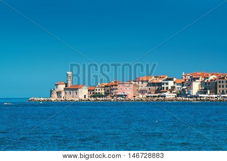 Picturesque old town Piran on Slovenian adriatic coast shot from sailing boat on sunny summer day