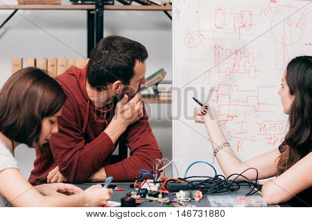 Wiring diagram discussing at laboratory. Young engineers creating new model of electronic construction, experimental research of ways of connecting cables on scheme